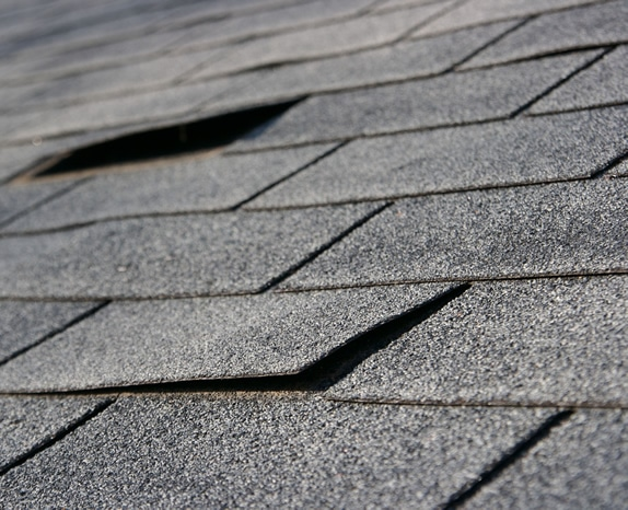 Asphalt roofing shingles with damages shingles from storm damage