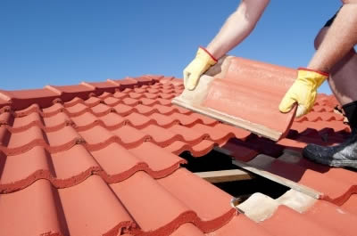 Contractor installing the last tile in a ceramic tile single roof