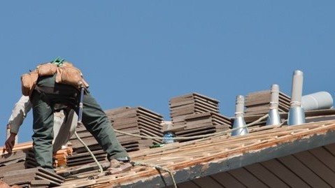 Contractor working on the installation of a new asphalt shingle roof on a residential home