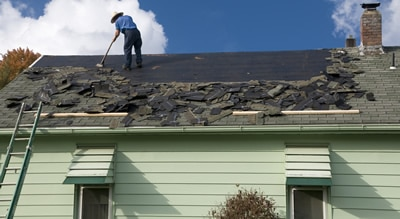 Removing old asphalt shingles to install a new roof
