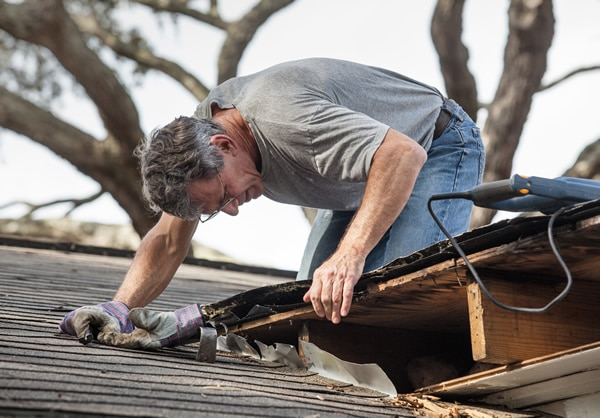 Roofer repairing a storm damaged roof