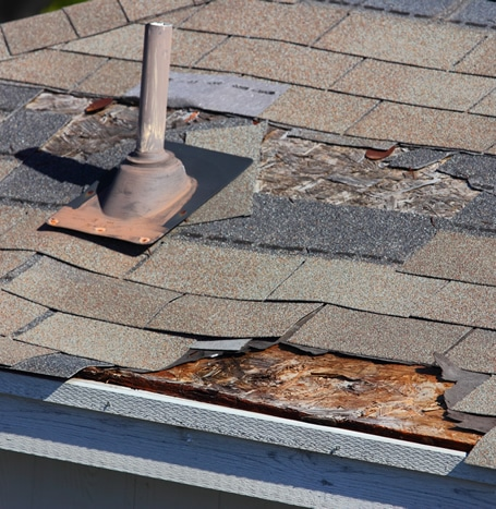 Storm damaged roof with missing shingles and damaged base